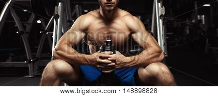 Young muscular guy sitting with a bottle of water in the gym. Bodybuilder man with a shaker. Muscular Man Resting After Exercise And Hold From Shaker. Sports and fitness. Fitness man in the gym.