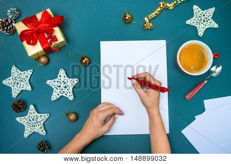 The top view of female hands with pen and Christmas decorations