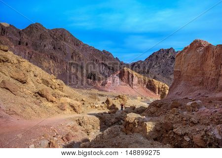 Dry stone desert near the southern seaside resort of Eilat. Woman photographer on a dirt road at the foot of King Solomon