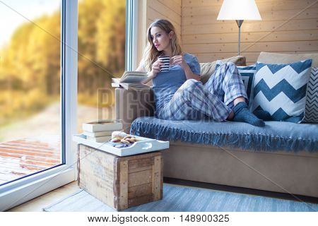 Young beautiful blonde woman with cup of coffee and book sitting home by the window. Autumn fall trees view. Lazy day off concept