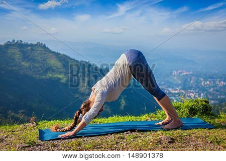 Yoga outdoors. Young sporty fit woman doing Ashtanga Vinyasa Yoga asana Adho mukha svanasana - downward facing dog - in Surya Namaskar Sun Salutation outdoors in Himalayas in the morning