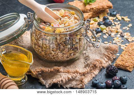 Homemade granola with honey and granola bar on black background