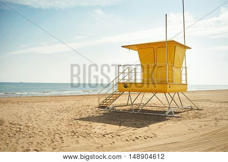 Footprints and wheeltracks on the sand beyond an empty yellow lifeguard cabin on a deserted beach