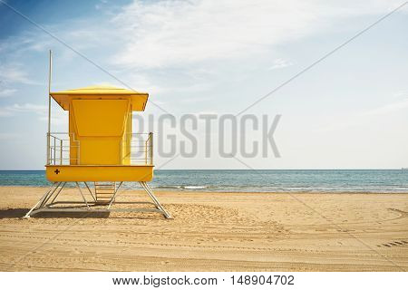 Quiet blue sky and sea and a saturated yellow lifeguard post on a deserted beach in beautiful weather