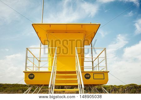 Close up ground level shot of a closed yellow lifeguard post on the background of blue sky with some clouds