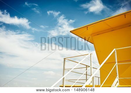 Roof and railings of a sunny yellow lifeguard booth with blue sky and white clouds