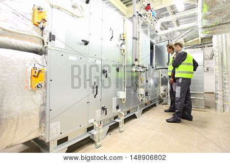 Workers in electrical switchgear room of CNC plant