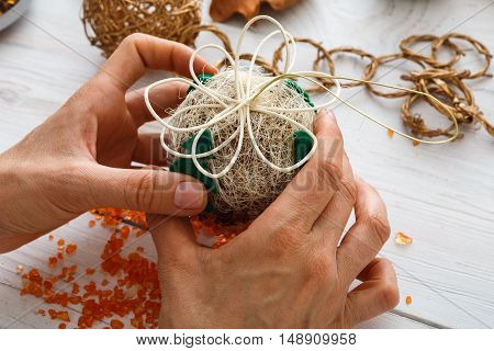 Creative diy craft hobby. Making handmade craft christmas ornaments and balls with felt spruce tree. Woman's leisure, holiday decorations. Closeup of female hands at white wood background