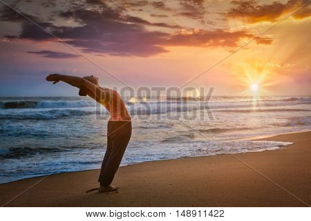 Young sporty fit woman doing yoga Sun salutation Surya Namaskar pose Hasta Uttanasana on tropical beach on sunset. With lens flare