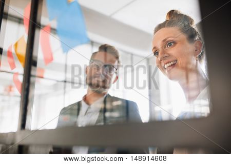 Two Professionals Looking Over Adhesive Notes
