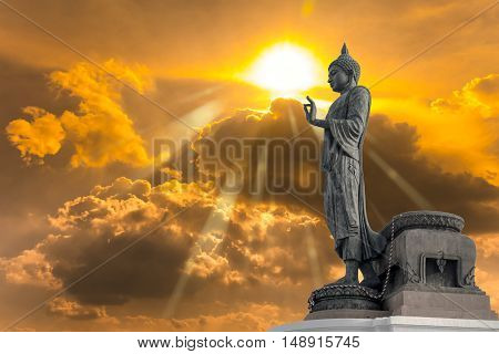 Buddha statue against Golden sky with sunlight in background. Abstract Religion.