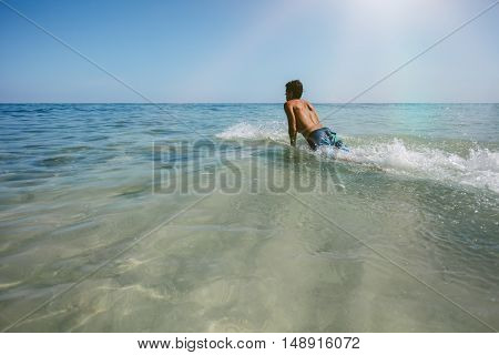 Shot of young man enjoying a surf in sea water. Male surfer in the ocean water with surf board. Man drifting on surfboard in the ocean