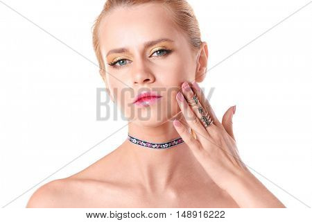 Young woman with choker on white background