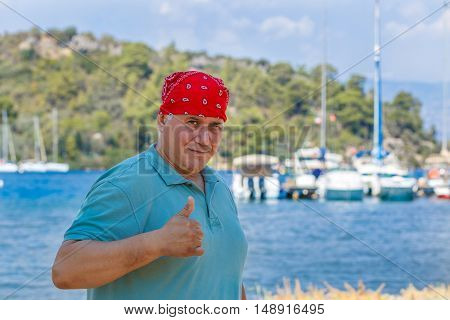 man in red bandana with raised thumb against the backdrop of marina Marmaris