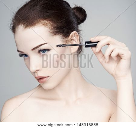 Beautiful woman. Mascara Applying.Eyes Make-up. Beautiful Spa model Girl with Perfect Fresh Skin. Youth and Skin Care Concept. Isolated on a gray background