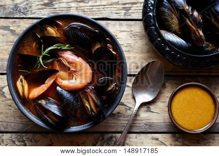 Bouillabaisse fish soup with prawns, mussels tomato, lobster. Sauce Rouille. Traditional France, Italian, Spain dish. Rustic style background. Flat lay