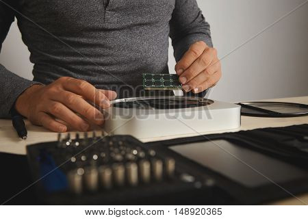 Athletic man in a dark gray henley shirt installing memory chips into computer