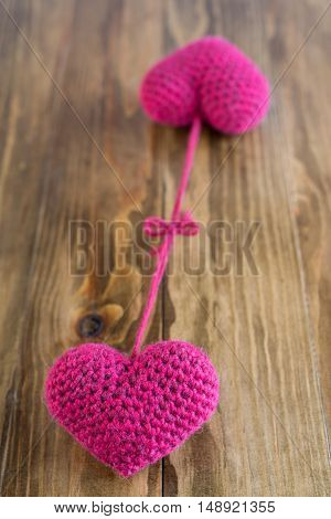 Two chrocheted hearts tied together on a wooden background. Soft focus on a nearest heart.