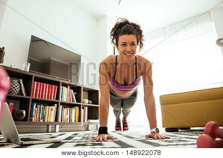 Attractive sportswoman doing push ups at home.