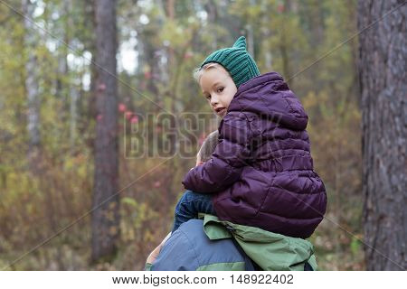 Little girl sitting on shoulders of her father in an autumn forest. She is looking at the camera. Soft focus on her face.
