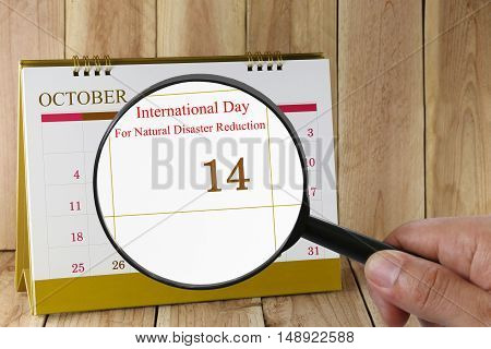 Magnifying glass in hand on calendar you can look International Day For Natural Disaster Reduction in 14 October concept of a public relations campaign fight against natural disasters.