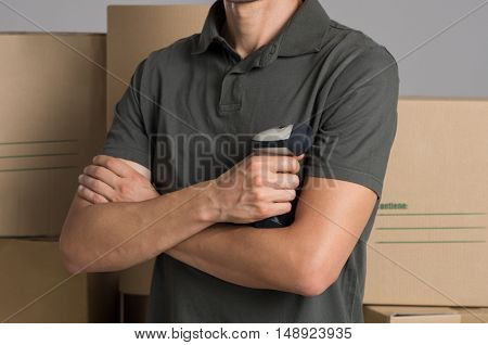 Close up of a young man holding barcode scanner at warehouse. Warehouse manager standing with folded hands holding barcode scanner. Courier man in front of boxes holding product scanner.