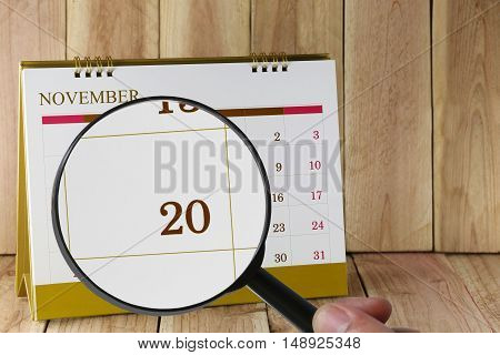 Magnifying glass in hand on calendar you can look Twentieth day of month. Focus number twenty in November. Concept in business and meetings.