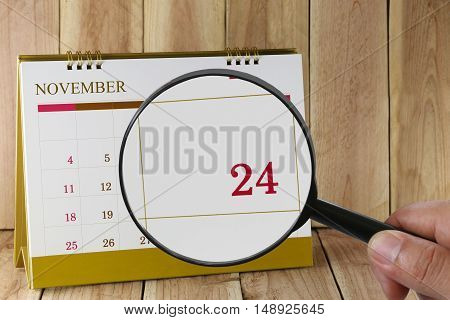 Magnifying glass in hand on calendar you can look Twenty-four days of monthFocus number Twenty-four in NovemberConcept in business and meetings.