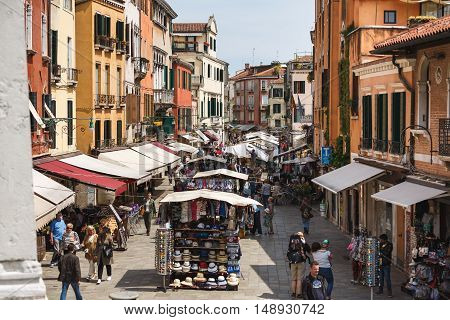Venice Italy - May 05 2016: The tourists crowd on a Campiello De L'anconeta street at spring time