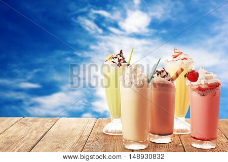 Delicious milkshakes on blue sky background