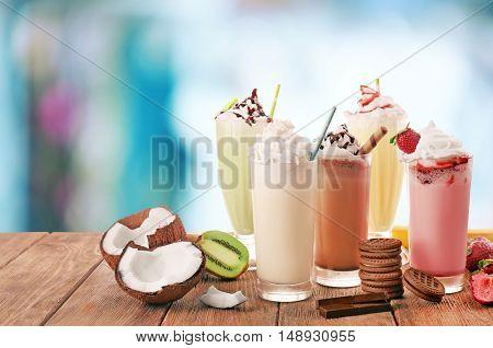 Delicious milkshakes on blurred background
