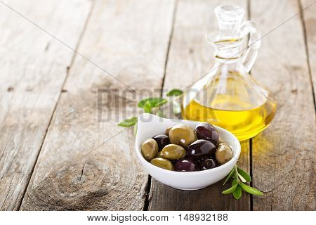 Olive oil in vintage bottle with black and green olives and leaves on rustic wooden background