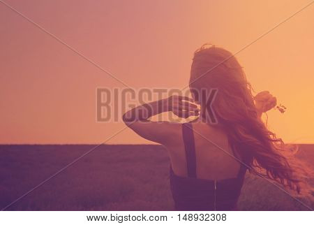 Silhouette Of A Young Woman With Long Hair Enjoying Beautiful Sunset In The Lavender Field. Back Vie