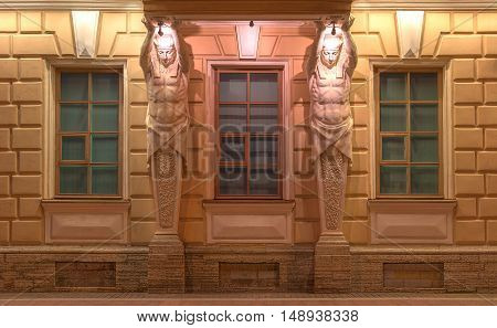 St. Petersburg Russia - August 4 2016: Three windows in a row and sculptures on night illuminated facade of Russian Maritime Register of Shipping front view