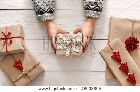 Creative hobby. Woman's hands show christmas holiday handmade present in craft paper with twine ribbon. Holding xmas gift box, decorated with snowflake, on white wooden table background, top view.