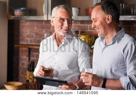 Old experienced manager showing his collegue new material on tablet while having a drink in the kitchen