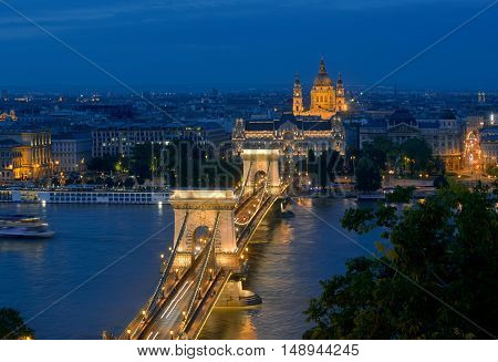Chain Bridge (Budapest Hungary) night view. Illuminated Saint Stephen's Basilica in background.
