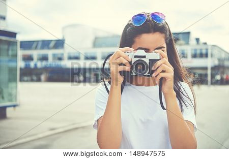 Young woman with her sunglasses perched on her head standing outdoors photographing the camera on a bright summer day