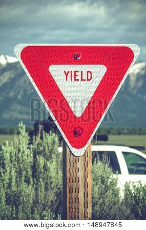 Large red yield sign in a countryside with mountains