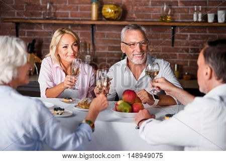 Calm and happy. Middle-aged couple listening for toasting at table