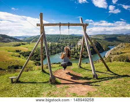 Beautiful girl on the swing with panoramic view on Vojvodina, Serbia.