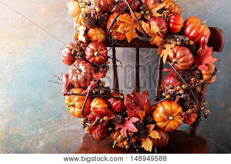 Festive autumn wreath with pumpkin and fall leaves on an antique chair