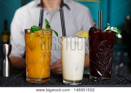 Closeup of three creative sweet exotic non-alcoholic party cocktails in restaurant at bar background. Glasses on bar table refreshing drinks with straws.