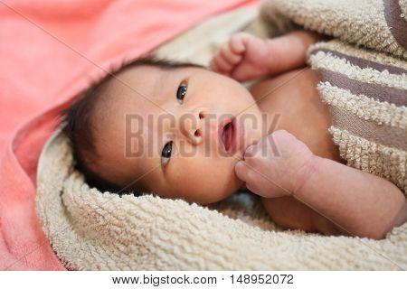 suspicious baby boy facial expressions on the bedAsian boy in Thailand.