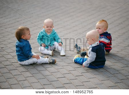 photo of cute little children sitting in the circle