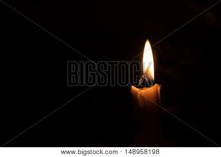 One light candle burning brightly image is isolated against a black background and fades into a shadow.