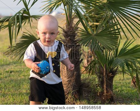 Happy mother with cute baby boy having tropical vacation on Maldives. Kid playing among palm trees.