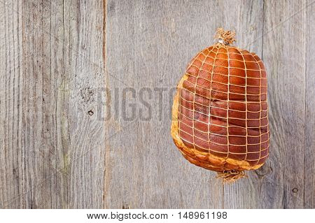 Smoked boneless pork ham hock wrapped in netting on a weathered wood background
