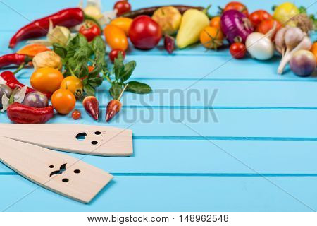 Fresh organic vegetables with wooden spoons and stirrers on blue background.Space for text.