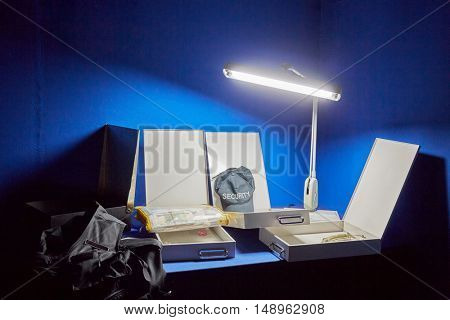 Table with boxes with keys, money pack, cap and jacket under bright lamp in dark room.